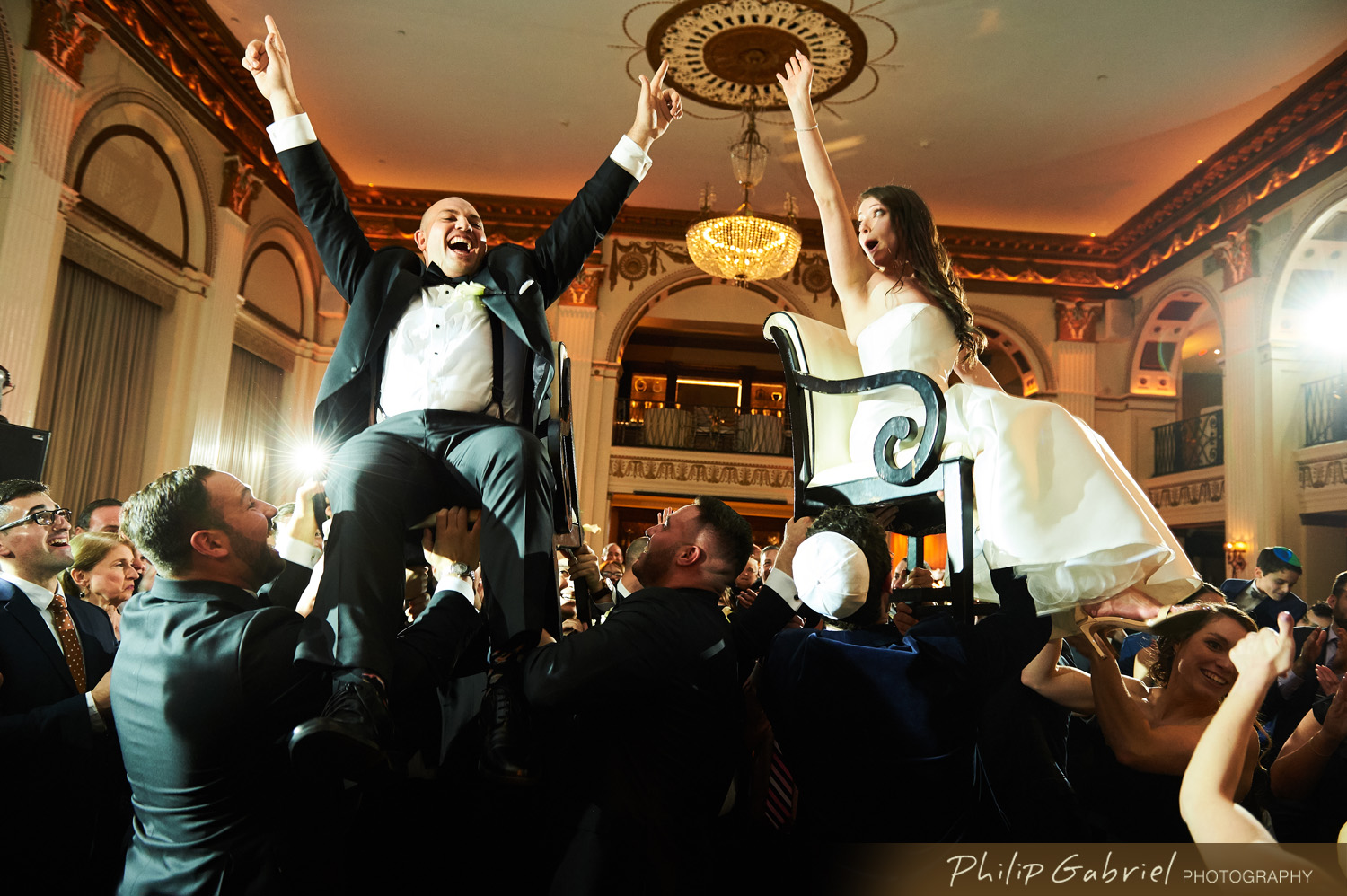 jewish wedding bride and groom up on the chairs