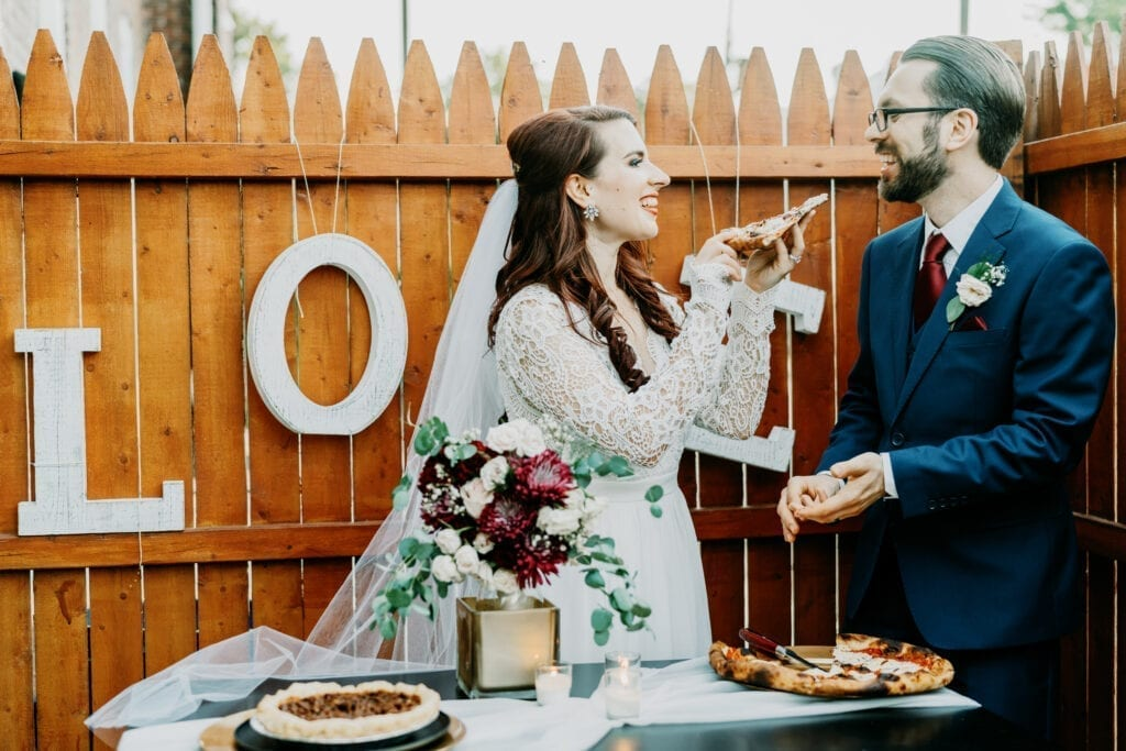 bride feeding her groom pizza