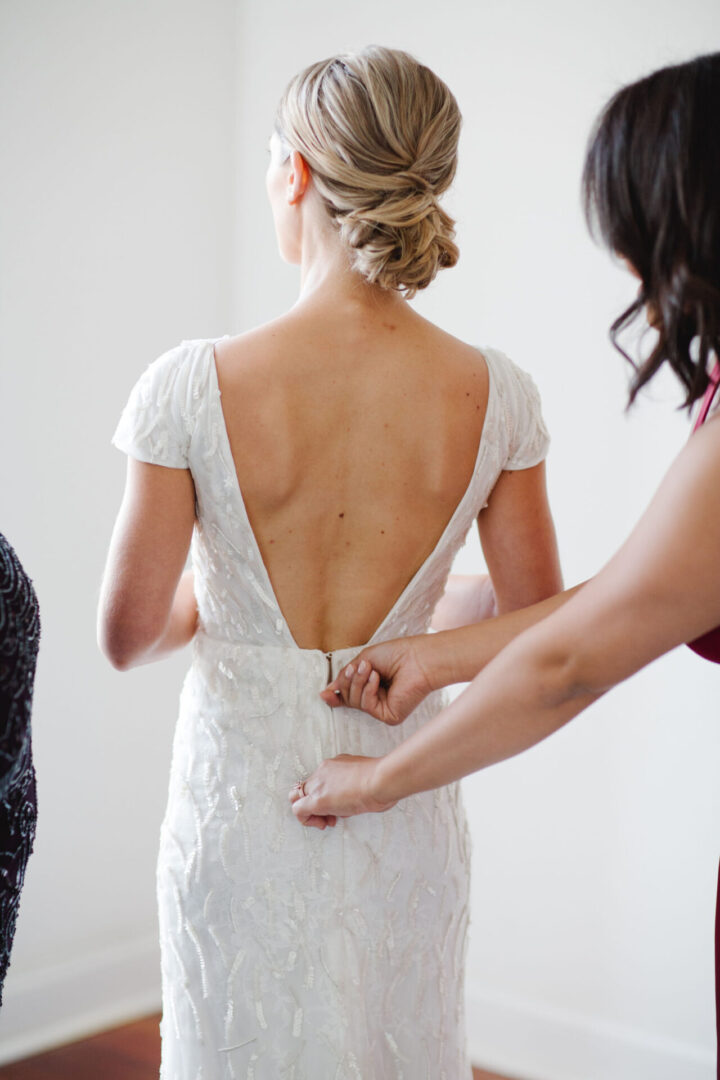 beautiful bride getting into her gown with updo hairstyle