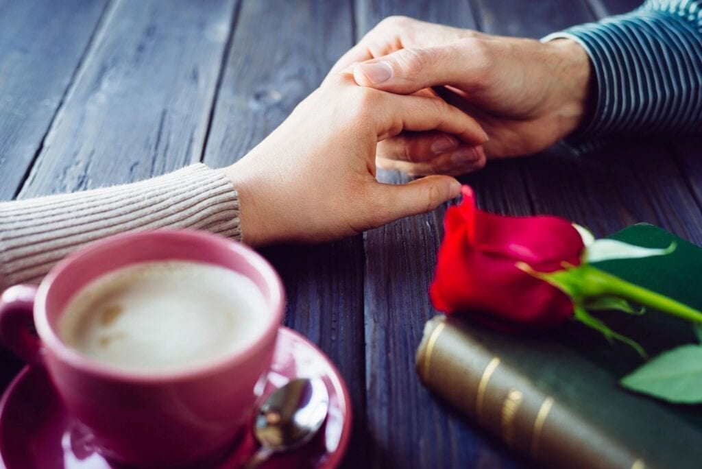 couple holding hands over coffee Strong Love